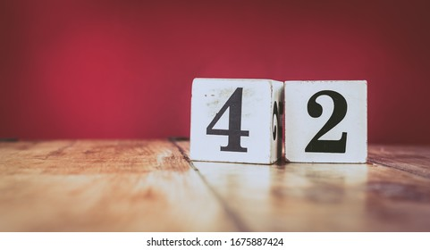 Number 42 on a vintage wooden table and dark maroon background - retro style white blocks