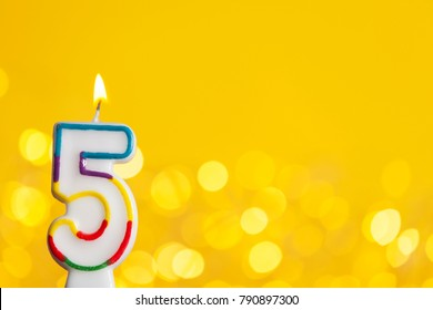 Number 5 birthday celebration candle against a bright lights and yellow background