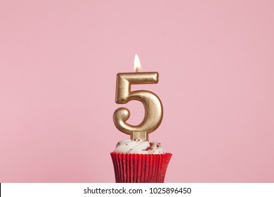 Number 5 gold candle in a cupcake against a pastel pink background