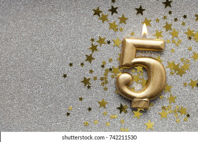 Number 5 gold celebration candle on star and glitter background