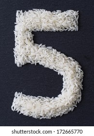 Number 5 made of rice on a black slate