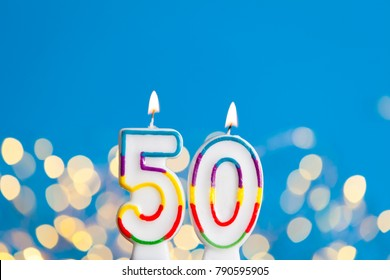 Number 50 birthday celebration candle against a bright lights and blue background