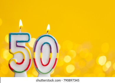 Number 50 birthday celebration candle against a bright lights and yellow background