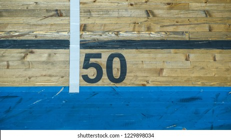 Number 50 in black on natural wood with blue stripe beneath