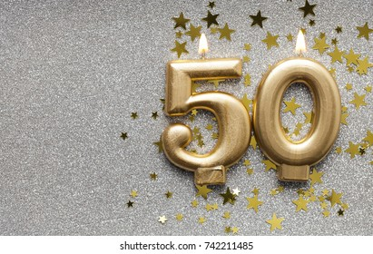 Number 50 gold celebration candle on star and glitter background