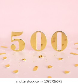 The number 500 is gold numbers on a pink background and golden confetti. Space for text.