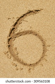 The number 6 drawn on sand at the beach,