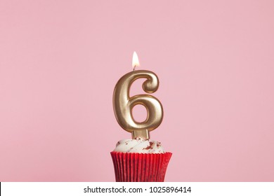 Number 6 gold candle in a cupcake against a pastel pink background