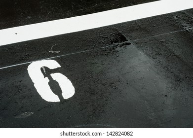 "The number ""6"" printed on the wet road. closeup"