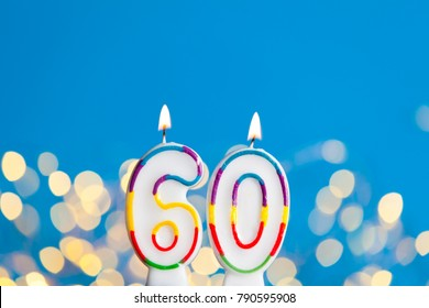 Number 60 birthday celebration candle against a bright lights and blue background