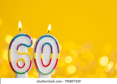 Number 60 birthday celebration candle against a bright lights and yellow background