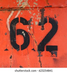 number 62, black stencil letters on grunge, red metal background