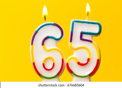 Number 65 birthday celebration candle against a bright yellow background