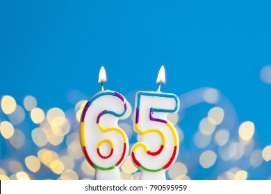 Number 65 birthday celebration candle against a bright lights and blue background