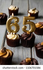 Number 65 celebration birthday cupcakes on a wooden background