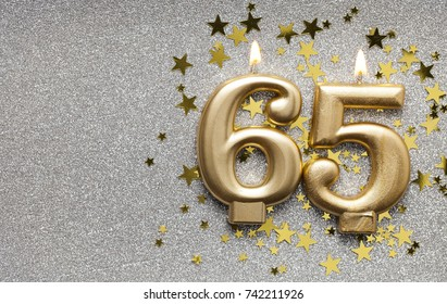 Number 65 gold celebration candle on star and glitter background