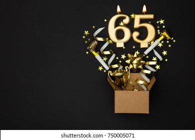 Number 65 gold celebration candle and gift box background