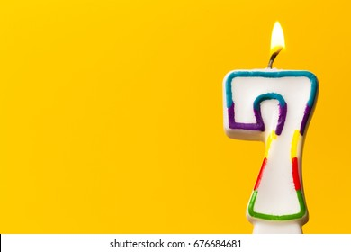 Number 7 Birthday Celebration Candle Against A Bright Yellow Background