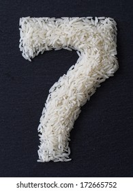 Number 7 made of rice on a black slate