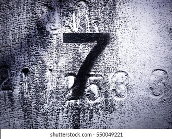 number 7 written on wet carbon black stone wall