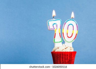 Number 70 birthday candle in a cupcake against a blue background