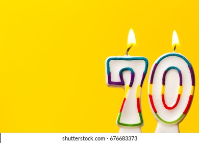 Number 70 birthday celebration candle against a bright yellow background