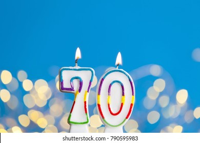 Number 70 birthday celebration candle against a bright lights and blue background