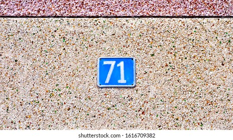 Number 71, seventy-one, a blue plate centered on rough light tone background.