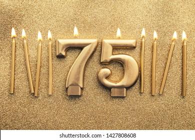 Number 75 gold celebration candle on a glitter background