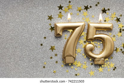 Number 75 gold celebration candle on star and glitter background
