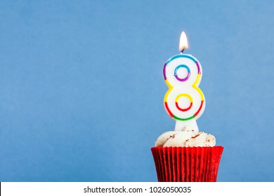 Number 8 birthday candle in a cupcake against a blue background