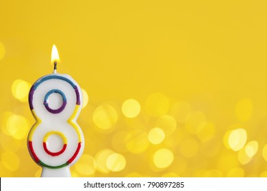 Number 8 birthday celebration candle against a bright lights and yellow background