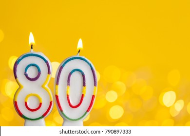 Number 80 birthday celebration candle against a bright lights and yellow background