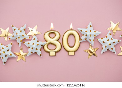 Number 80 gold candle and stars on a pastel pink background