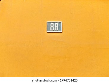 Number 88, eighty-eight, small blue plate on warm yellow wall.