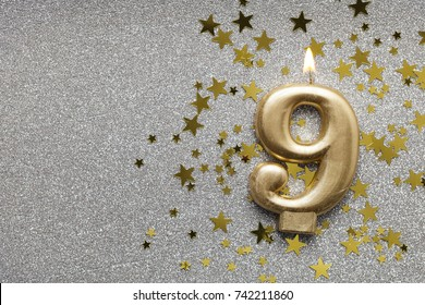 Number 9 gold celebration candle on star and glitter background