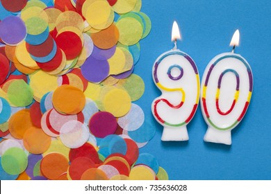 Number 90 celebration candle with party confetti