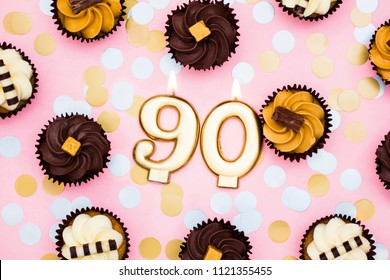 Number 90 gold candle with cupcakes against a pastel pink background