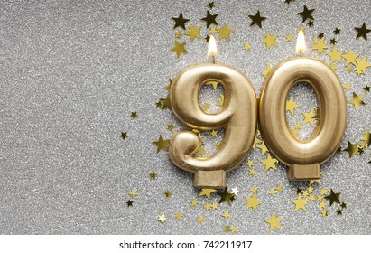 Number 90 gold celebration candle on star and glitter background