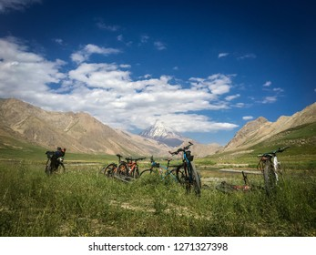 A number of bikes are in a wide green plain and Mount Damavand in the background.