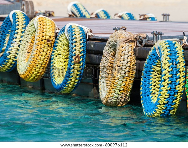 A number of colorful tires used on the pier as bumpers for boats.