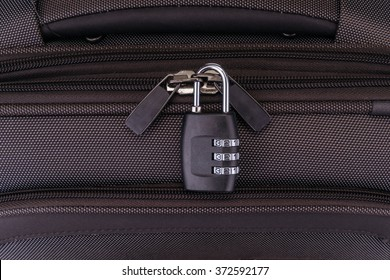 Number combination padlock on the gray suitcase.
