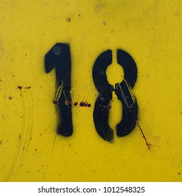 number eighteen, 18, black stencil number on yellow background