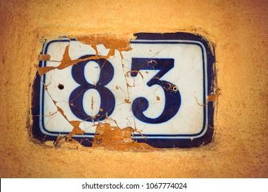 Number eighty three enamel door number on plaster wall