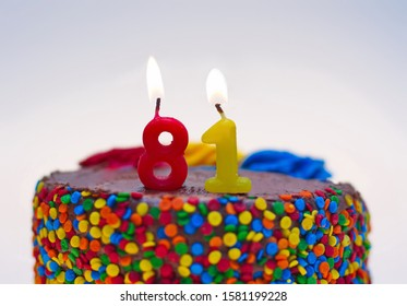 Number eighty-one candle lit on top of a chocolate confetti cake