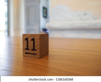 number eleven wooden cube on the wood table