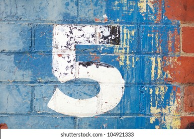 The number five painted on a carpark wall