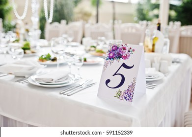 Number five at table for guests on wedding hall.