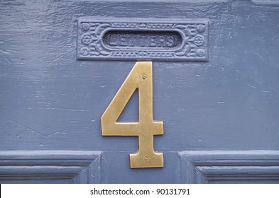 The number four in brass attached to a house front door