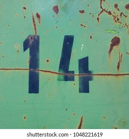 number fourteen, black stencil letters on rusty green metal background
